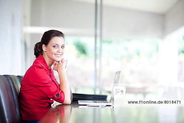 Young woman in office with laptop