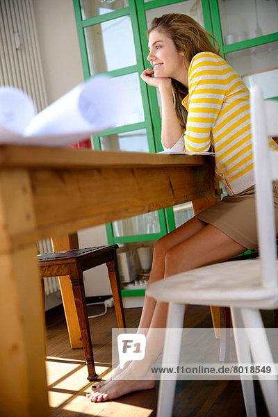 Junge Frau auf Tisch gelehnt mit Hand am Kinn
