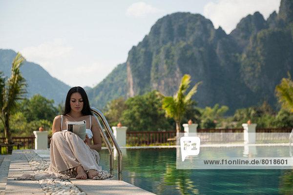 Frau sitzend lesend am Schwimmbad  Vang Vieng  Laos