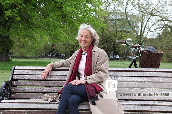 Seniorin auf Parkbank sitzend  Portrait