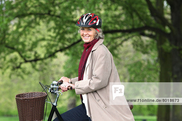 Seniorin auf dem Fahrrad im Park  Portrait
