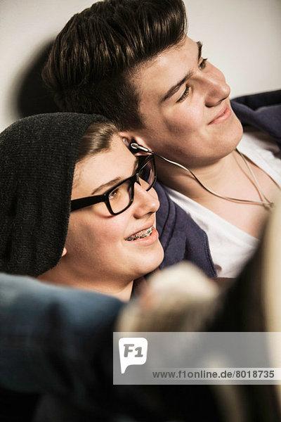 Zwei Jugendliche lächeln und hören Kopfhörer.