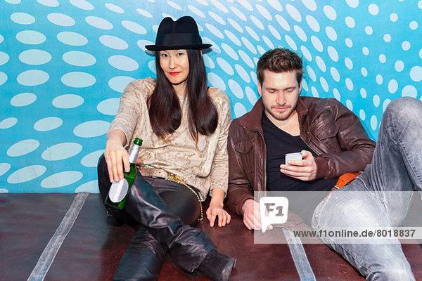 Paar sitzt auf dem Boden  hält Flasche Bier und Smartphone