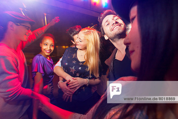 Group of people at party  man kissing woman's neck