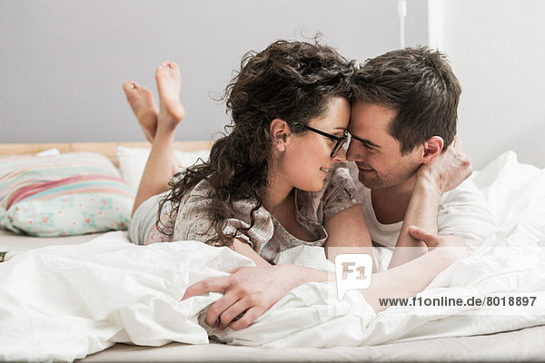 Mid adult couple wearing pyjamas lying on front on bed  face to face