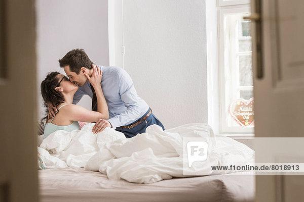 Mittleres erwachsenes Paar  das sich auf dem Bett küsst
