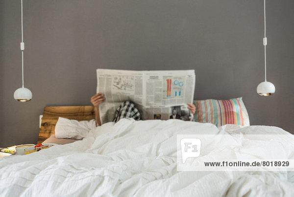 Mittleres erwachsenes Paar liest Zeitung im Bett  Gesichter verdunkelt