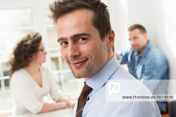Mature man smiling at camera  mid adults in background