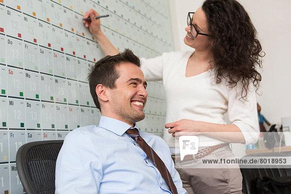 Frau schreibt auf Wandkalender  Mann sitzt auf Bürostuhl