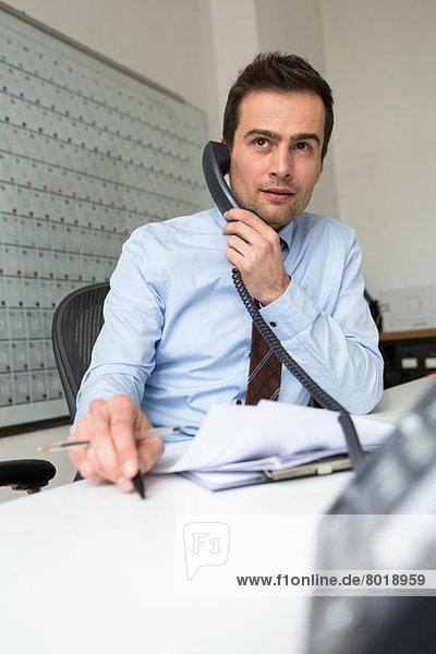 Geschäftsmann Multitasking  Telefonieren und Verwaltung