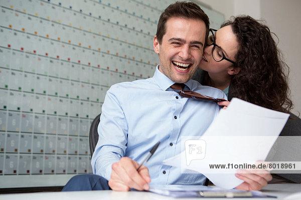 Frau küsst Geschäftsmann-Ohr