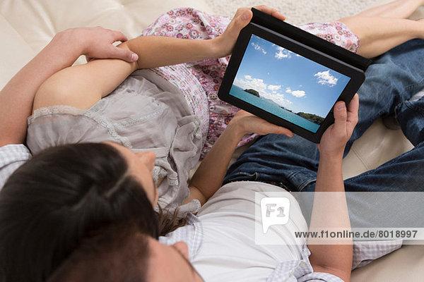 Mittleres erwachsenes Paar beim gemeinsamen Betrachten des digitalen Tabletts