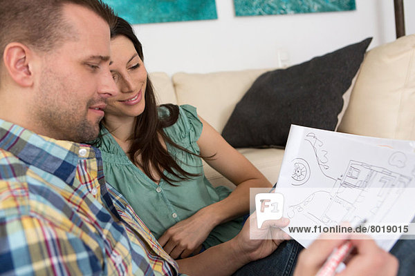 Mittleres erwachsenes Paar beim Skizzieren von Hausplänen