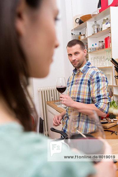 Mittlerer erwachsener Mann mit einem Glas Wein  Frau im Vordergrund