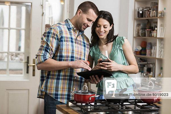 Mittleres erwachsenes Paar kochendes Abendessen  unter Verwendung der digitalen Tablette