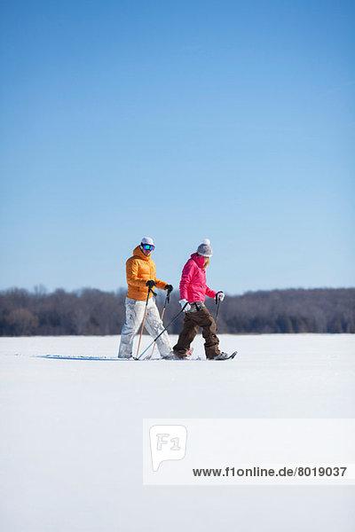 Erwachsenes Paar  das auf Schnee läuft Erwachsenes Paar, das auf Schnee läuft