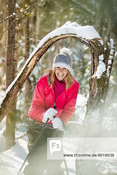 Junge erwachsene Frau unter schneebedeckten Ästen