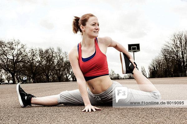 Frau macht Spagat mit nach hinten gebeugtem linken Bein
