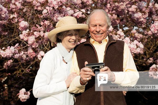 Mann und Frau lächelnd und mit Blick auf die Kamera in der Hand