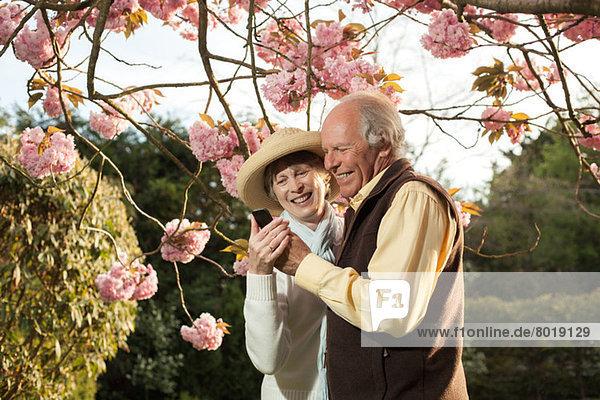 Seniorenpaar lächelt Nachricht auf dem Handy an