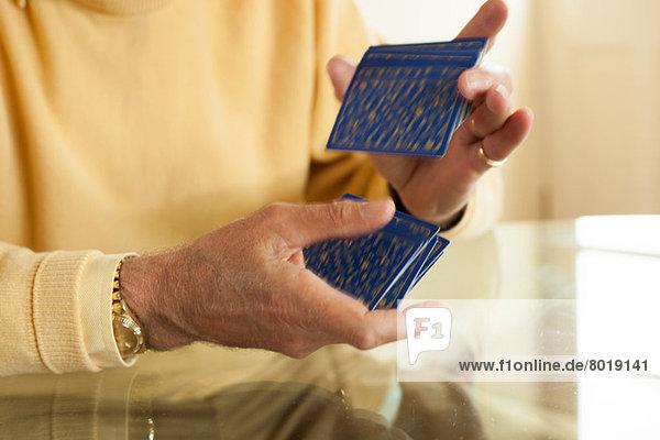 Nahaufnahme gealterter Hände beim Mischen von Spielkarten