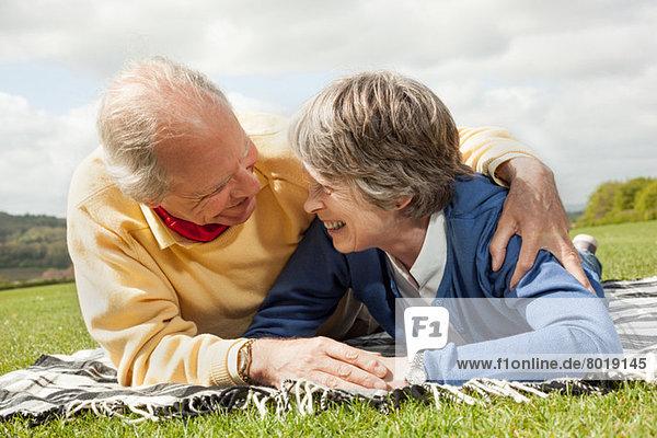 Mann und Frau liegen auf dem Bauch auf einer Decke im Feld.