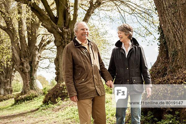 Mann und Frau halten sich an den Händen und gehen in den Park.