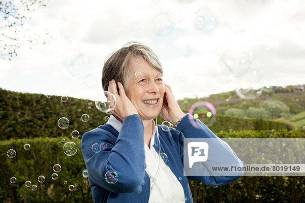 Seniorenfrau mit Ohren und Lachen über Blasen