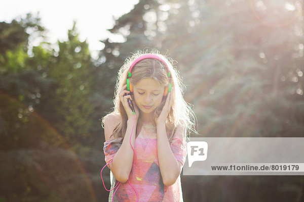 Teenagermädchen mit Kopfhörer im Sonnenlicht