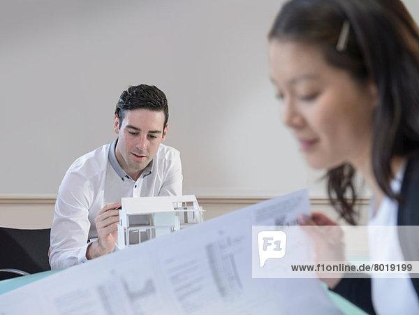 Architekten inspizieren Gebäudemodell und Pläne im Büro