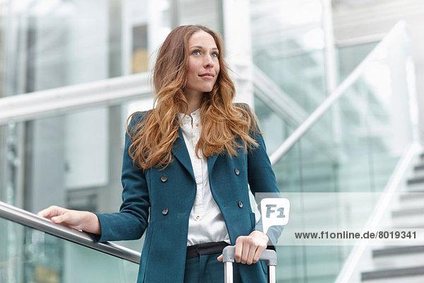 Junge Geschäftsfrau auf moderner Außentreppe