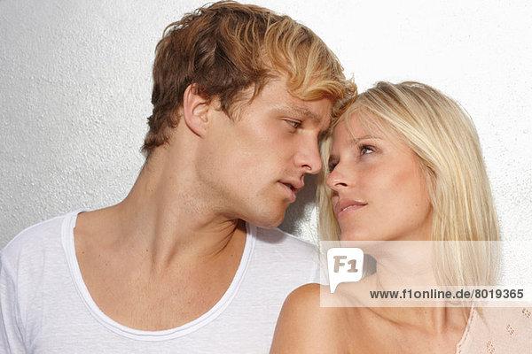 Porträt eines jungen Paares  das sich in die Augen schaut.