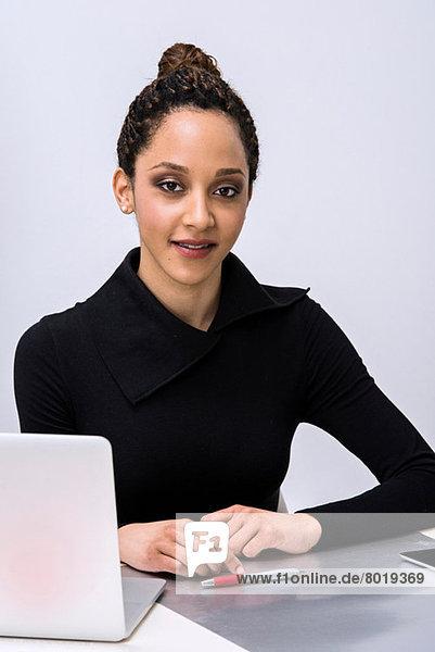 Portrait einer jungen Frau am Schreibtisch mit Laptop
