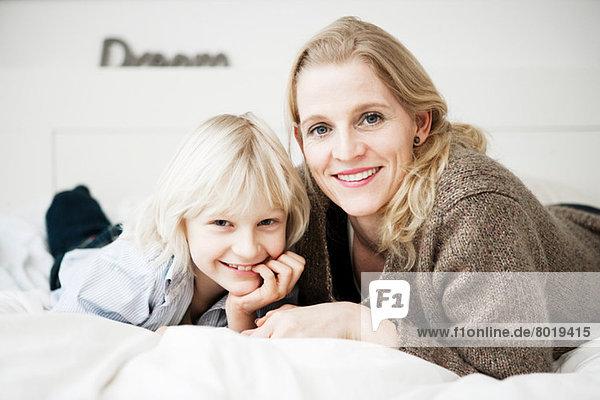 Porträt von Mutter und Sohn auf dem Bett liegend