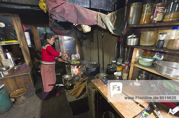 Eine einheimische Frau arbeitet in einer typischen nepalesischen Küche