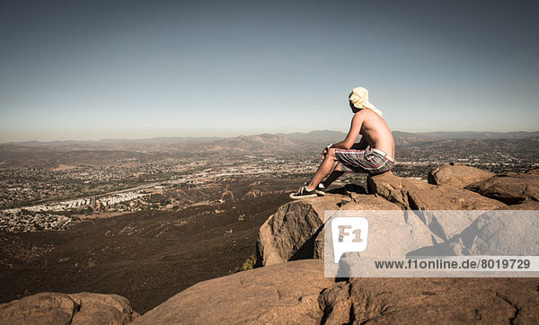 Man sitting on rock looking at view over San Diego  California  USA