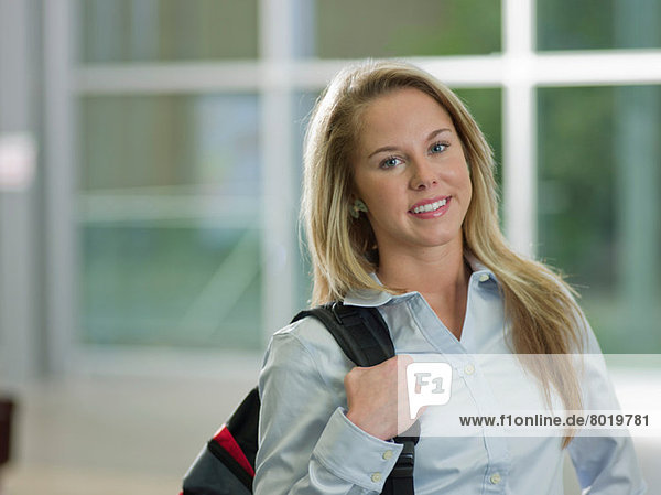 Young woman holding backpack smiling  portrait