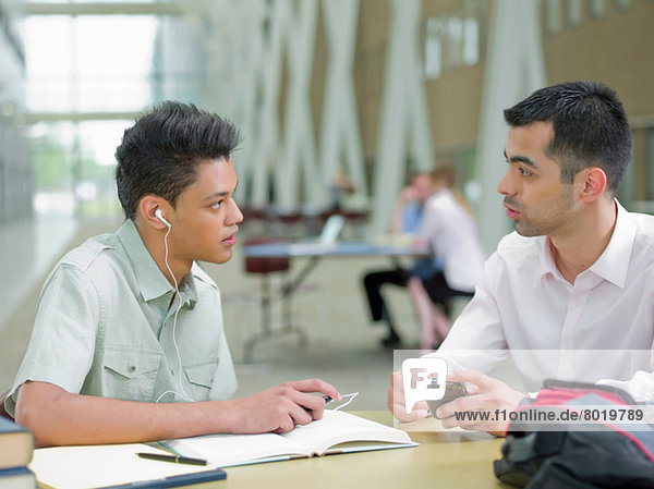 Young man studying with mid adult tutor
