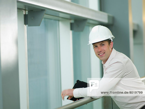 Mid adult construction worker in hard hat leaning on railing  portrait