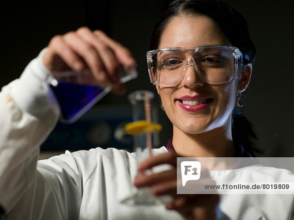 Young scientist in safety glasses mixing chemicals  smiling