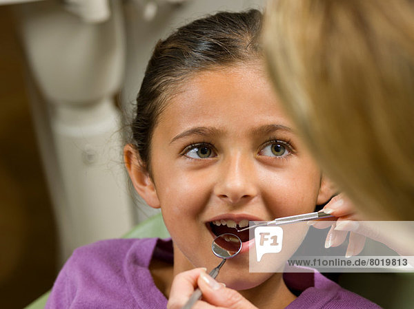 Dentist looking at young girl's teeth