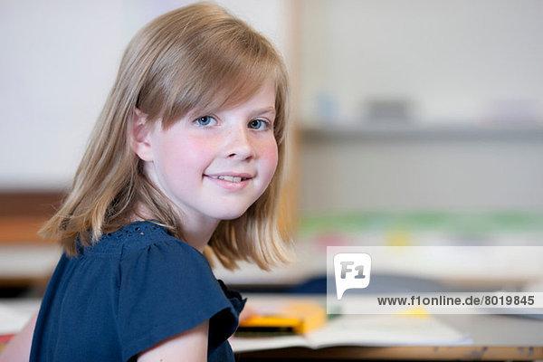 Schoolgirl sitting at desk in school and smiling  portrait