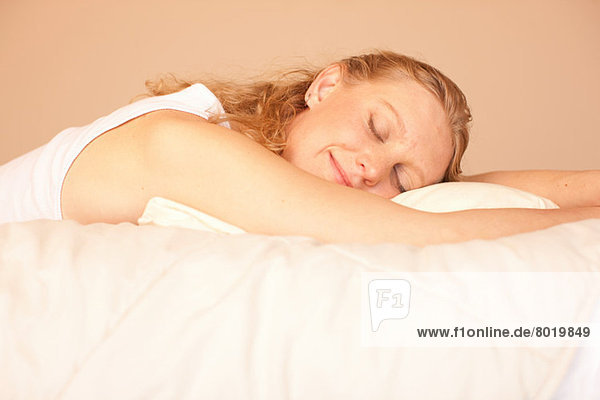 Mid adult woman sleeping on bed  smiling