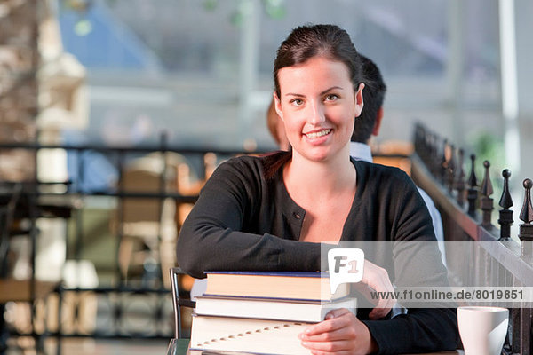Young student leaning on stack of books  portrait