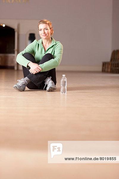 Mature woman sitting on floor  looking away