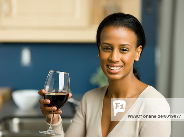 Young woman holding glass of red wine and smiling  portrait