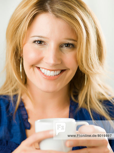 Mid adult woman holding cup and smiling  portrait