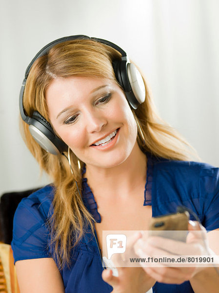 Mid adult woman wearing headphones and listening to mp3 player
