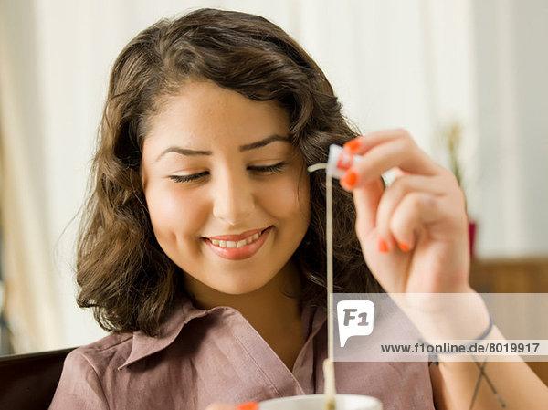 Junge Frau hebt Teebeutel aus der Tasse  lächelnd