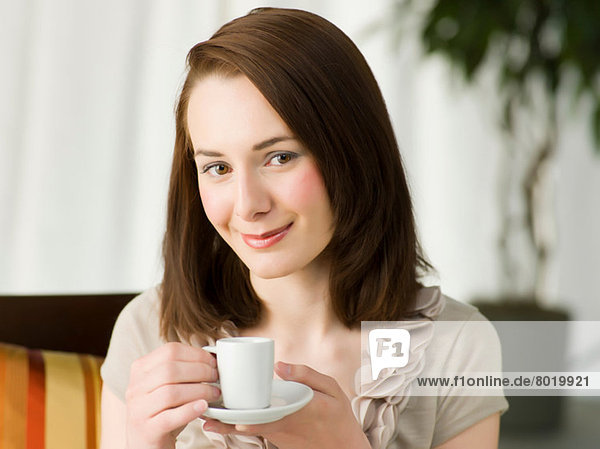Young woman holding coffee cup  portrait